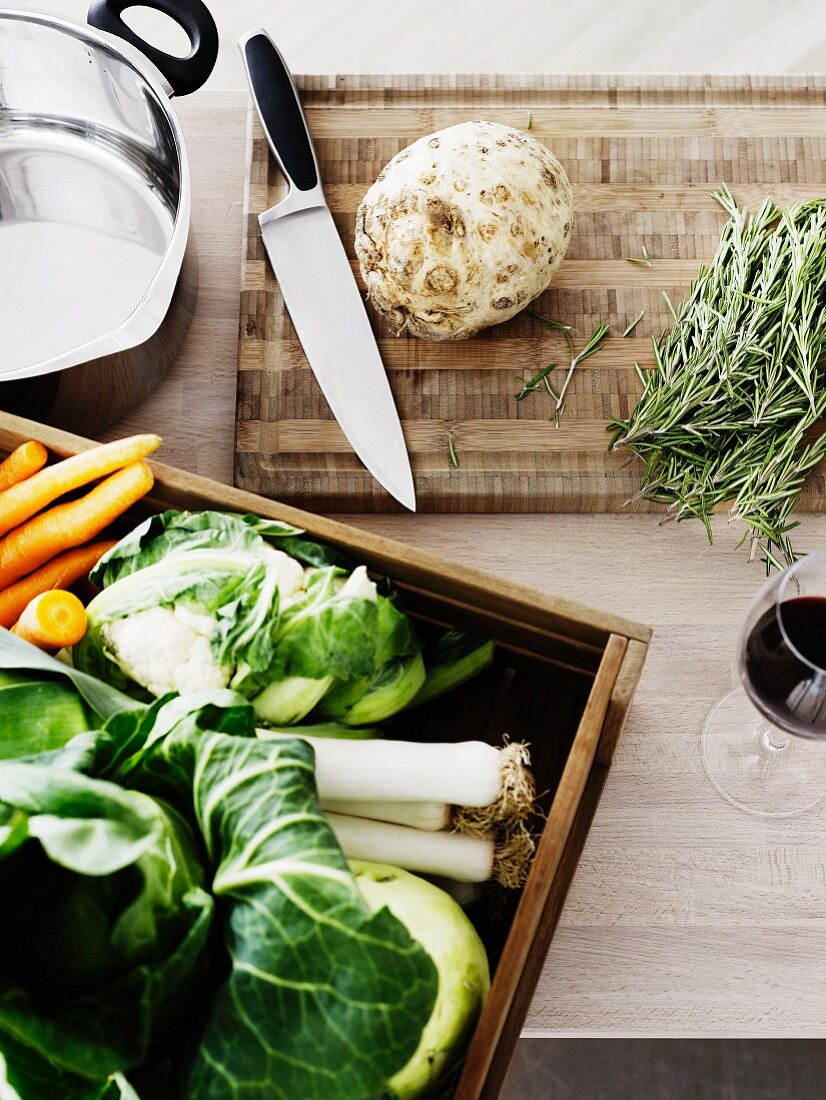 Fresh vegetables, rosemary and cooking utensils on a kitchen work surface