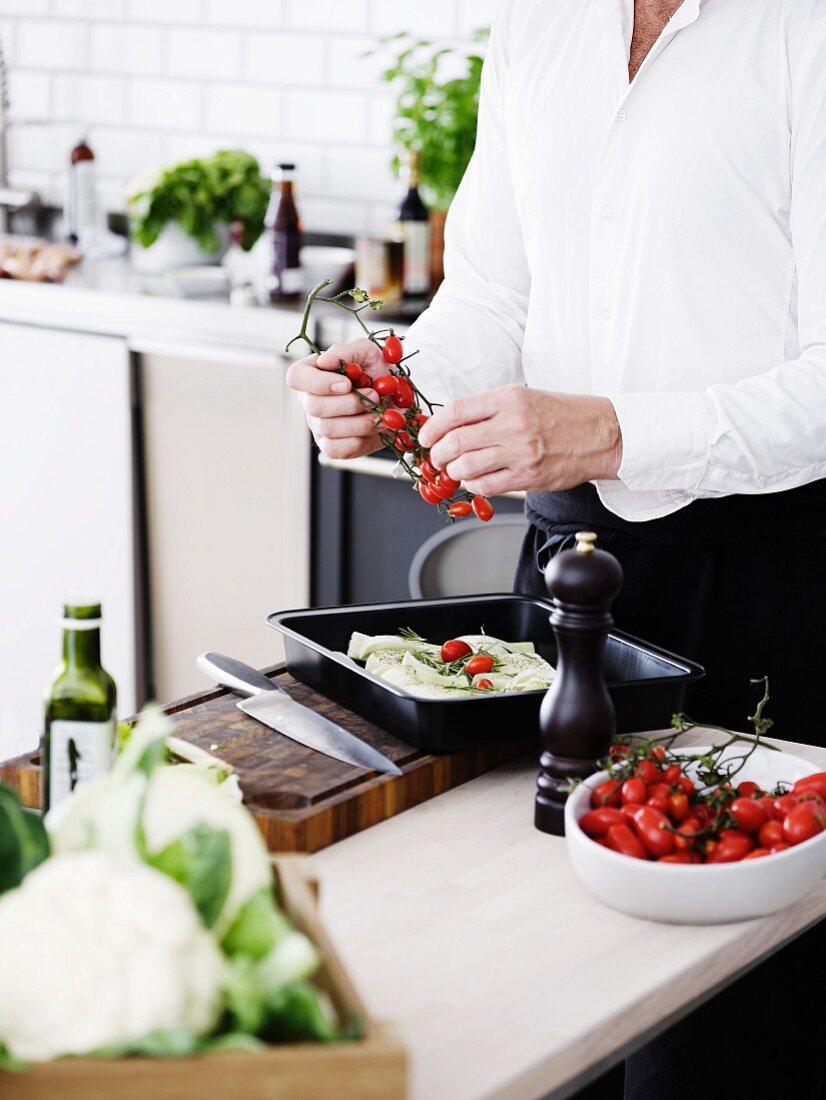 Mann in Küche streift Cocktailtomaten von der Rispe
