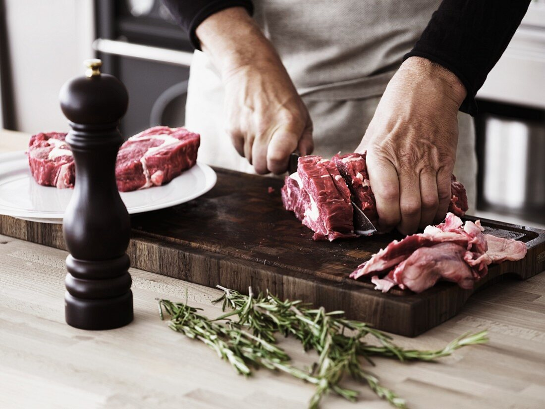 A man slicing a piece of beef into steaks