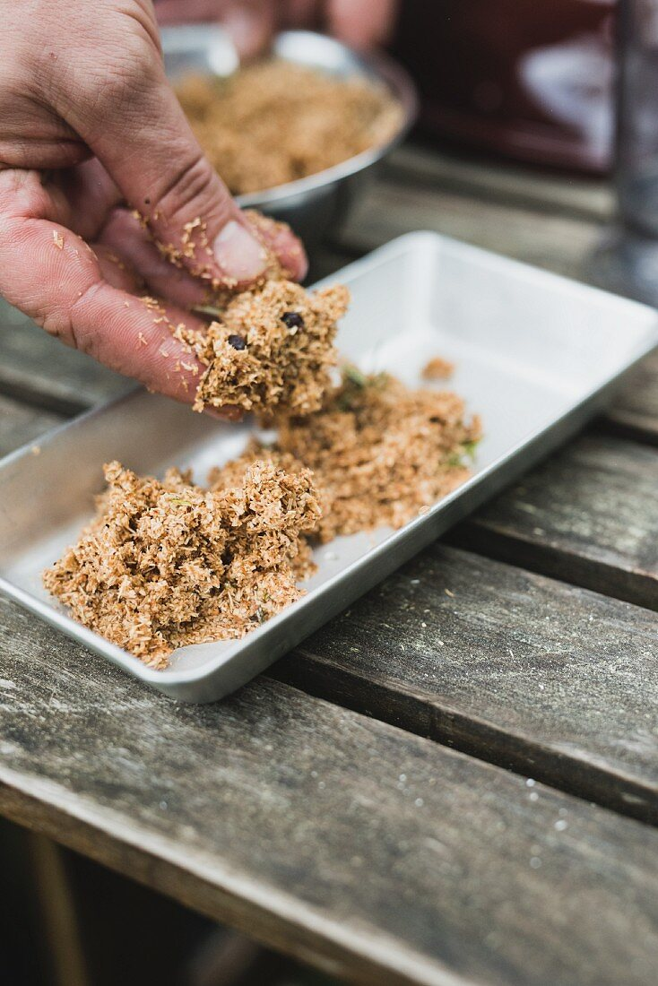 A soaked smoked mixture being transferred to an aluminium dish