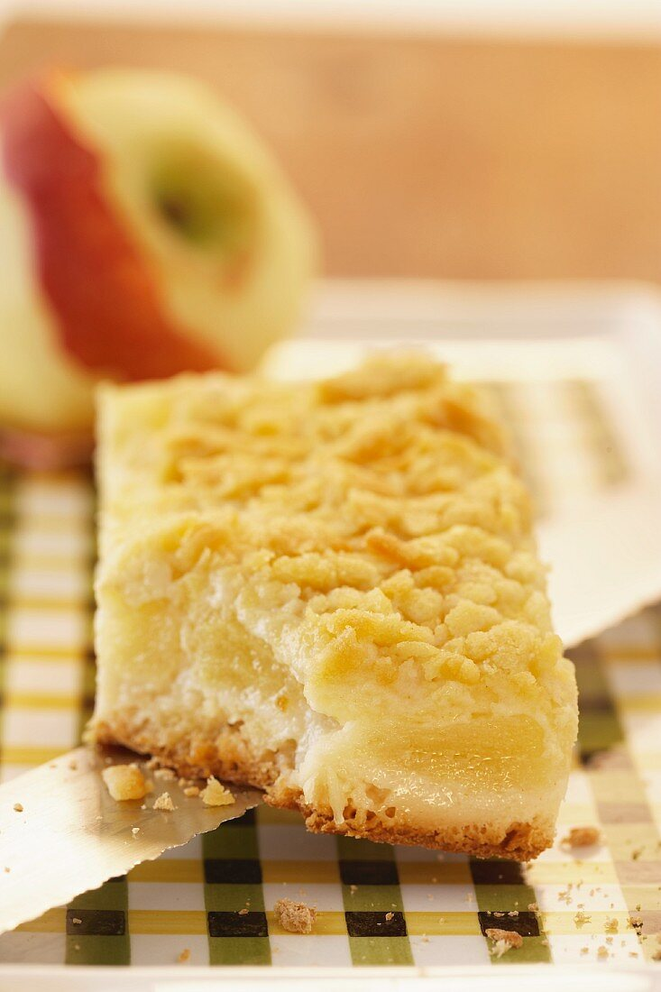 A slice of apple crumble cake with a bite taken out