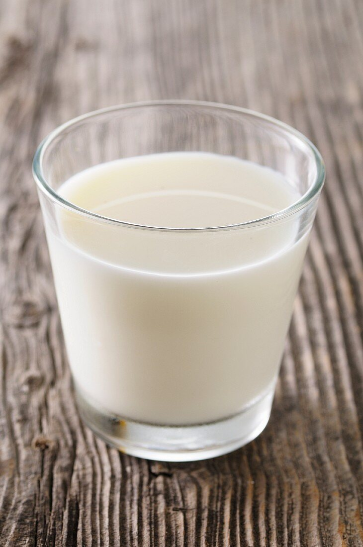 A glass of milk on a wooden surface