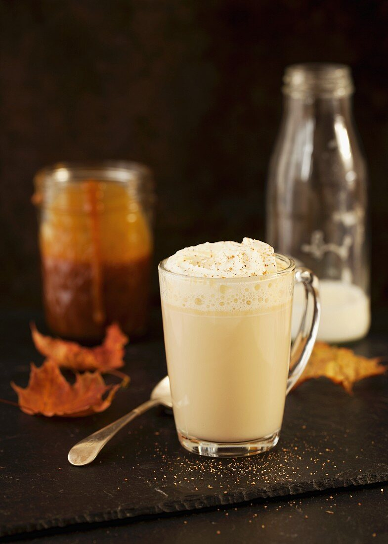 Caramel latte topped with whipped cream and nutmeg