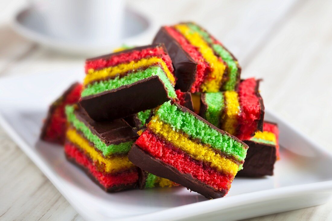 Colourful rainbow biscuits made with almond paste and chocolate glaze