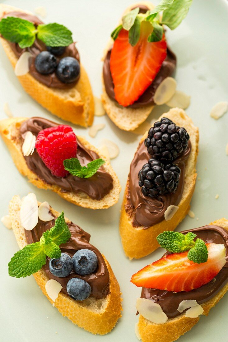 Baguette slices topped with nougat cream and berries as snacks for children