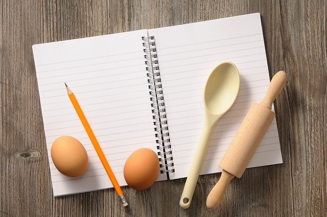 A notebook, kitchen utensils and eggs
