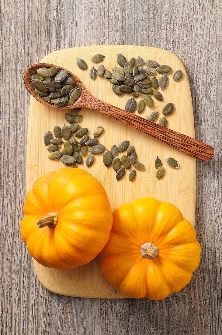 Pumpkin seeds and mini pumpkins on a chopping board