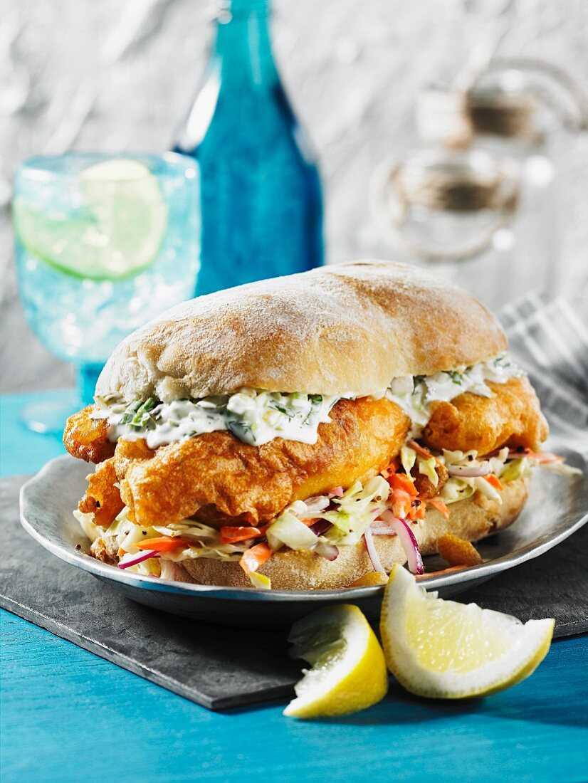 A fish sandwich with tartar sauce and coleslaw