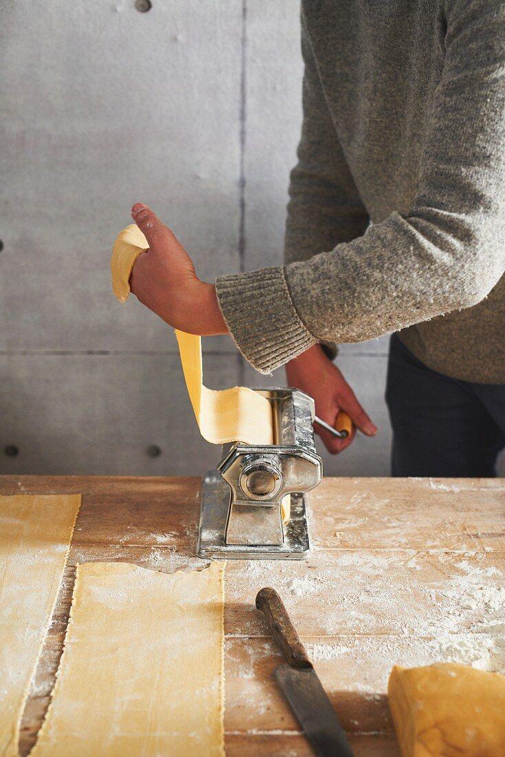 Passing pasta dough through a pasta maker