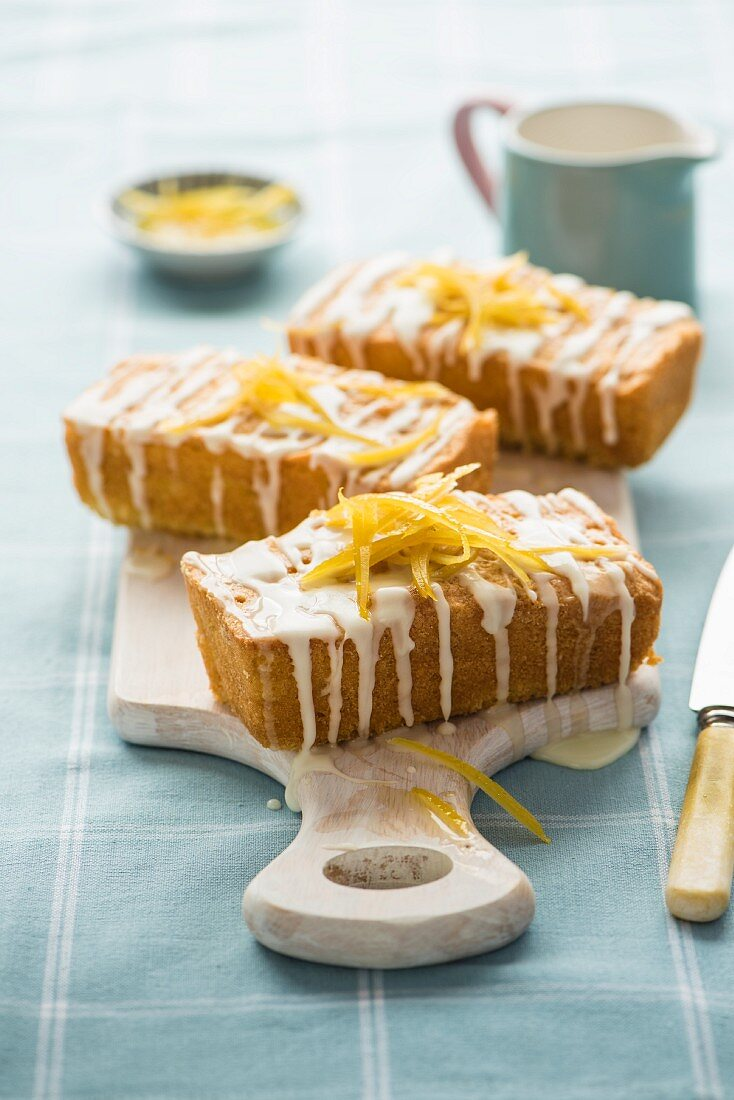 Three small iced lemon cakes with on a chopping board