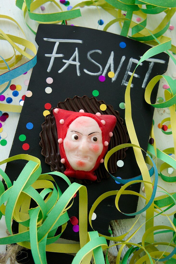 A marzipan carnival mask on a slate with paper streamers