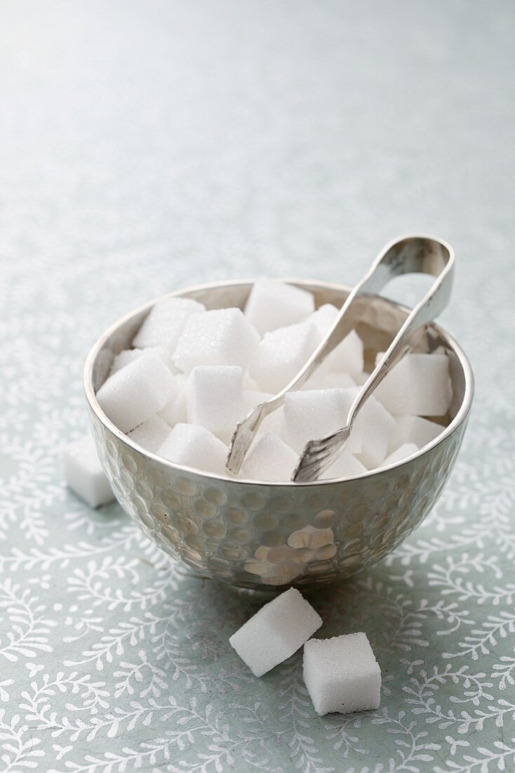 Sugar lumps and sugar tongs in a silver bowl