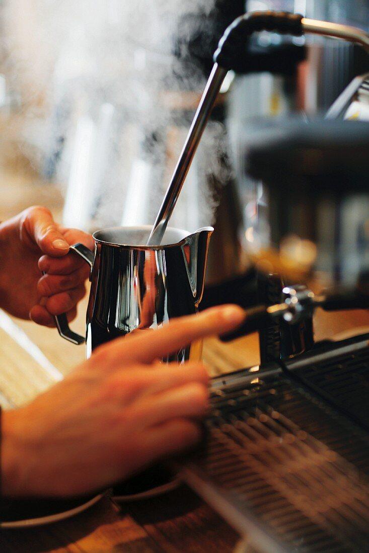 A barista foaming milk