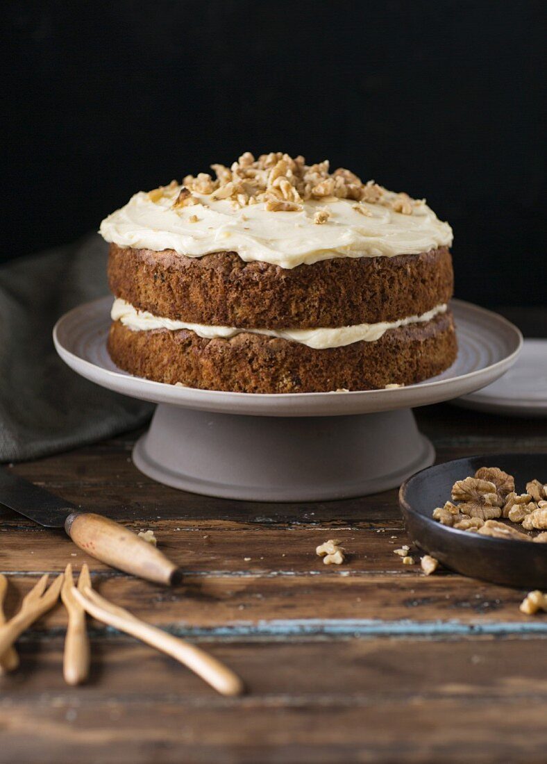 Carrot cake with a cream cheese frosting and chopped walnuts