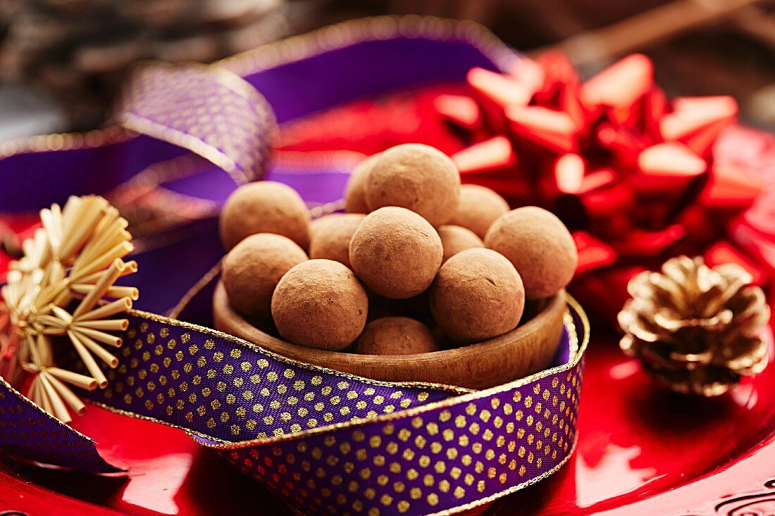 A bowl of chocolate truffles on a Christmas plate