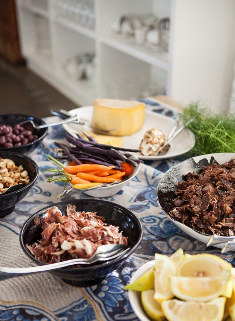 Brunch with meat dishes, vegetables and cheese