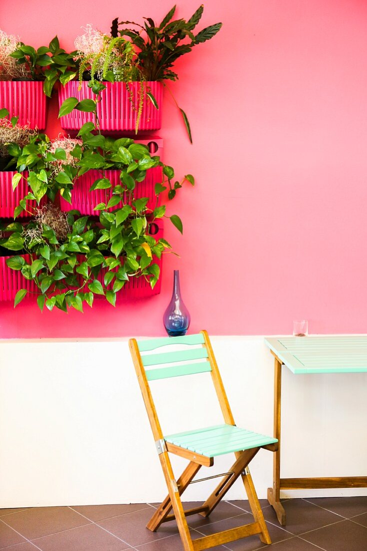 Chair and table below decorative planters mounted on wall in café Perlavia (Vienna, Austria)