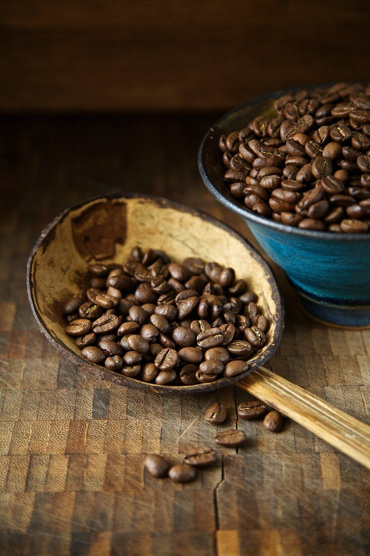 Organic coffee beans on a rustic spoon