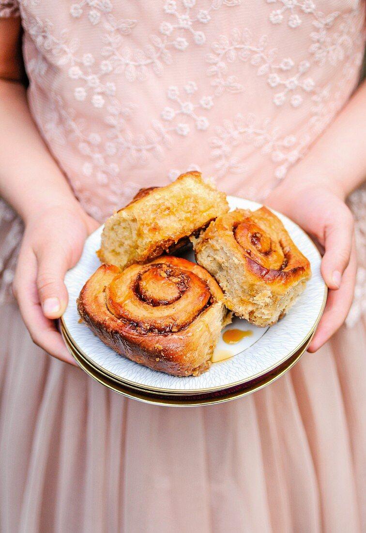 A little girl holding a plate of cinnamon buns