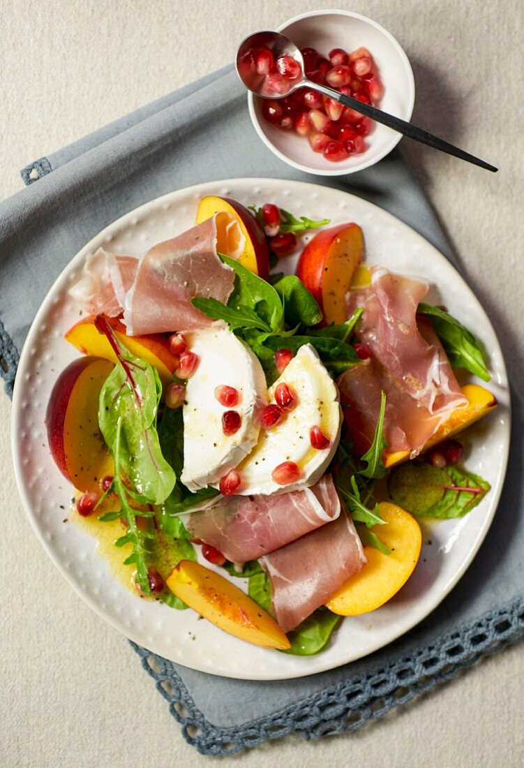 Parma ham salad with goat's cheese, nectarines and pomegranate seeds