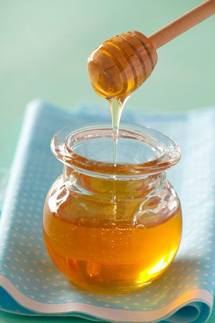 Honig fliesst von Honiglöffel in Glas