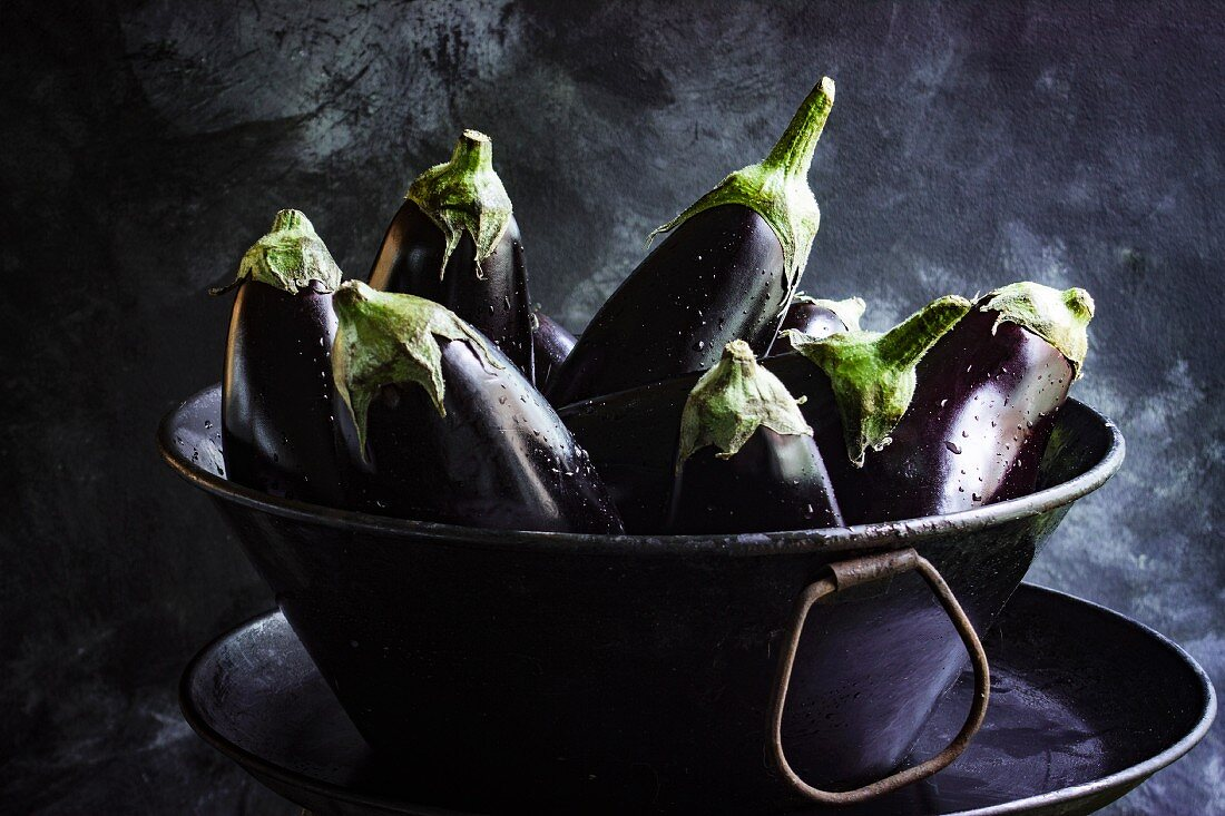 Fresh aubergines in a metal bowl