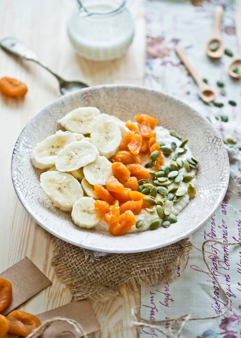 Millet flakes of almond milk, bananas, dried apricots and pumpkin seeds