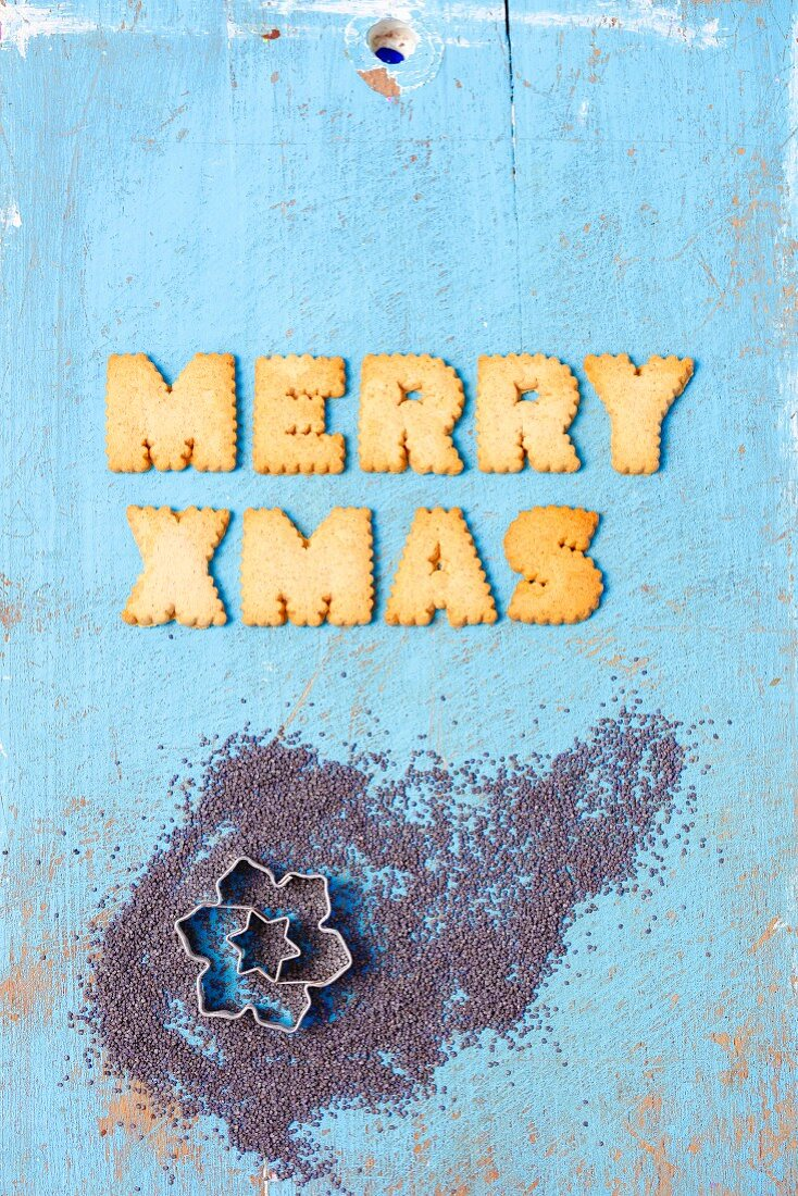 Christmas greetings written in English with biscuits and cutters in poppy seeds