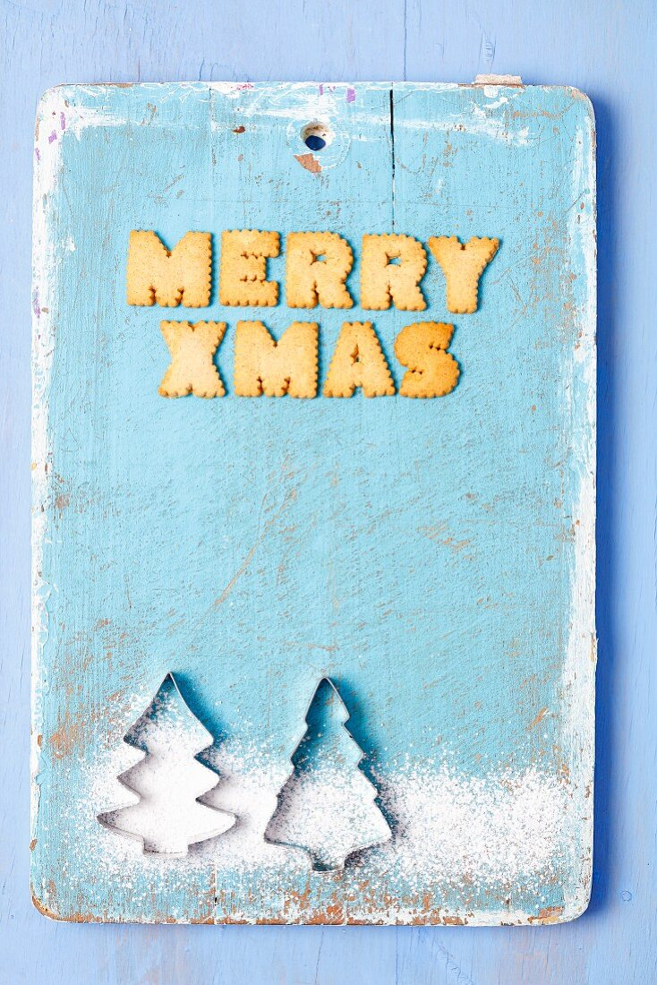 Christmas greetings written in English with biscuits and cutters