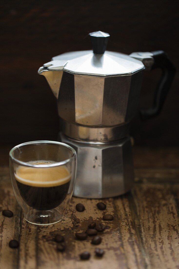 An espresso maker and a glass of espresso
