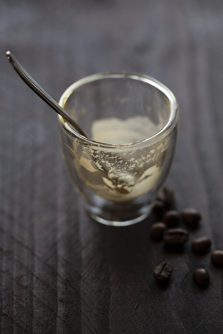 An empty espresso glass with a spoon on a wooden surface