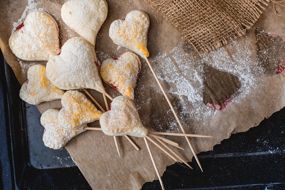 Heart-shaped jam-filled biscuits on sticks