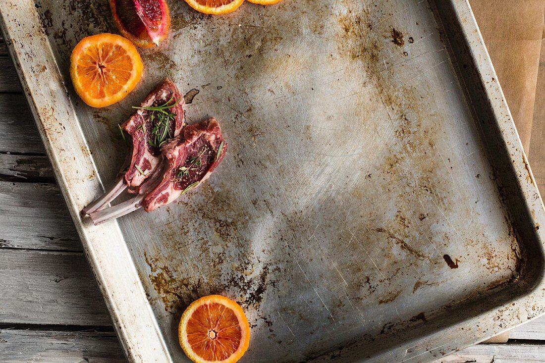 Two raw lamb chops with slices of blood orange on a baking tray (seen above)