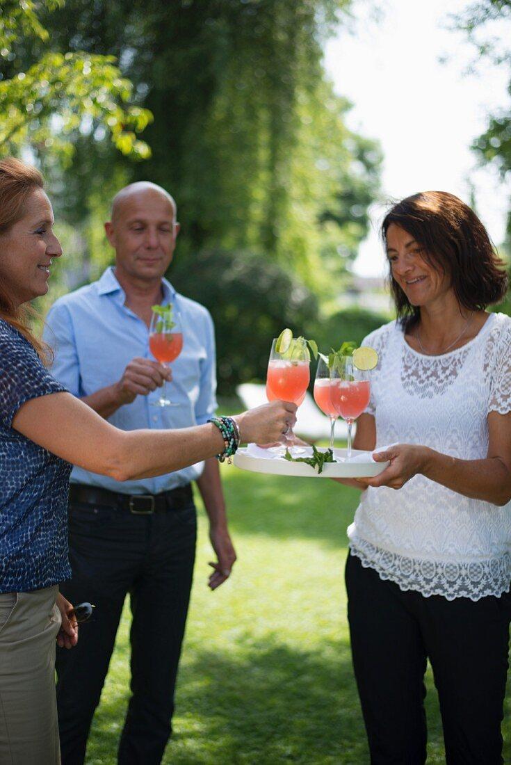 Three friends enjoying cocktails in garden