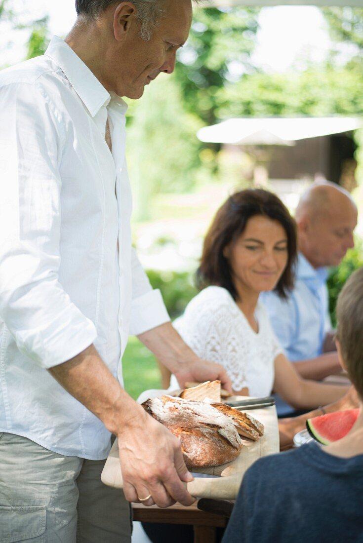 Man holding breadboard at brunch in garden
