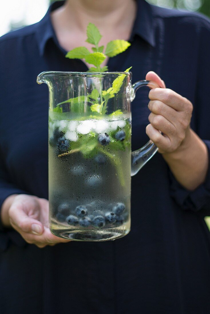 Refreshing drink with blueberries and herbs in glass jug