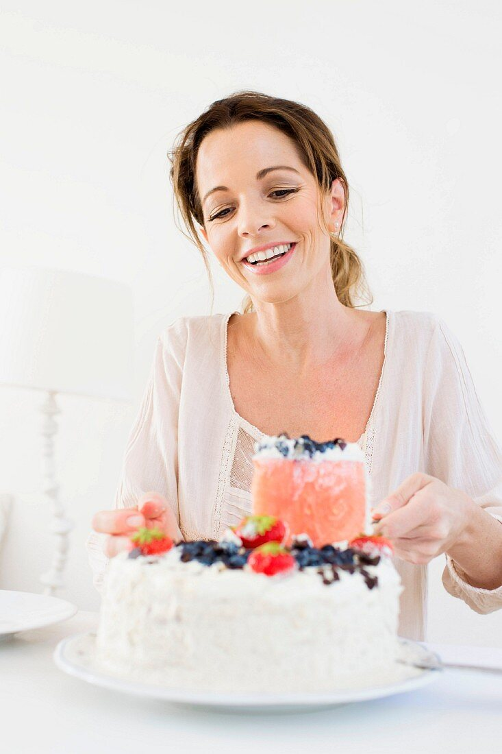 A woman taking a slice of berry cream cake