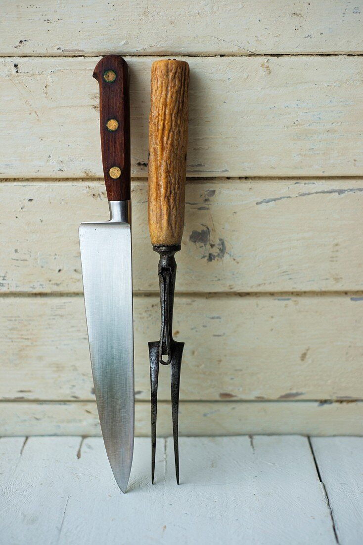 Carving cutlery against a wooden wall