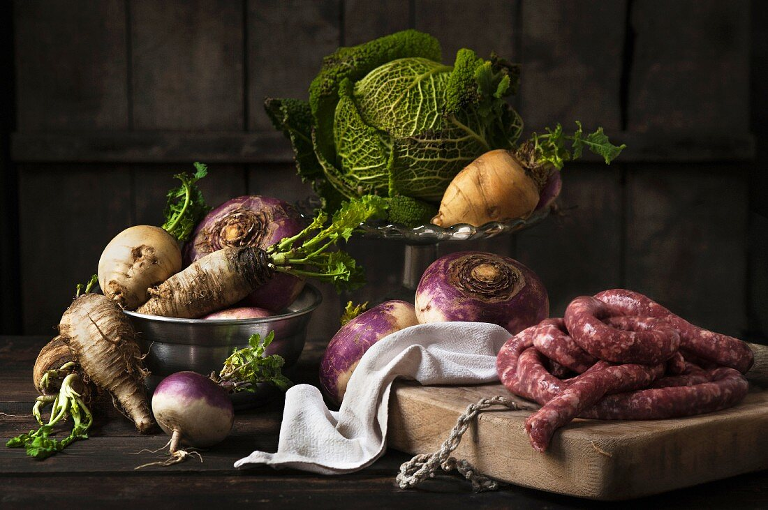 An autumnal arrangement featuring turnips, savoy cabbage and sausage