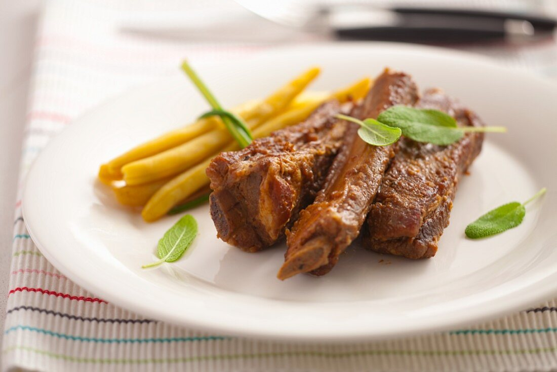Oven-baked ribs with yellow beans and sage