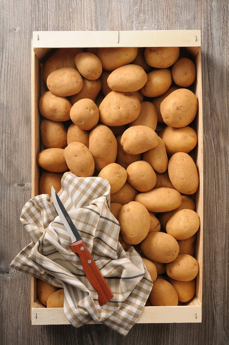 Potatoes in a crate with a tea towel and a knife