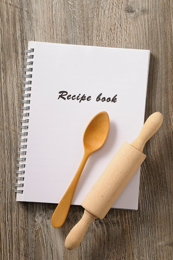 A recipe book, a wooden spoon and a rolling pin