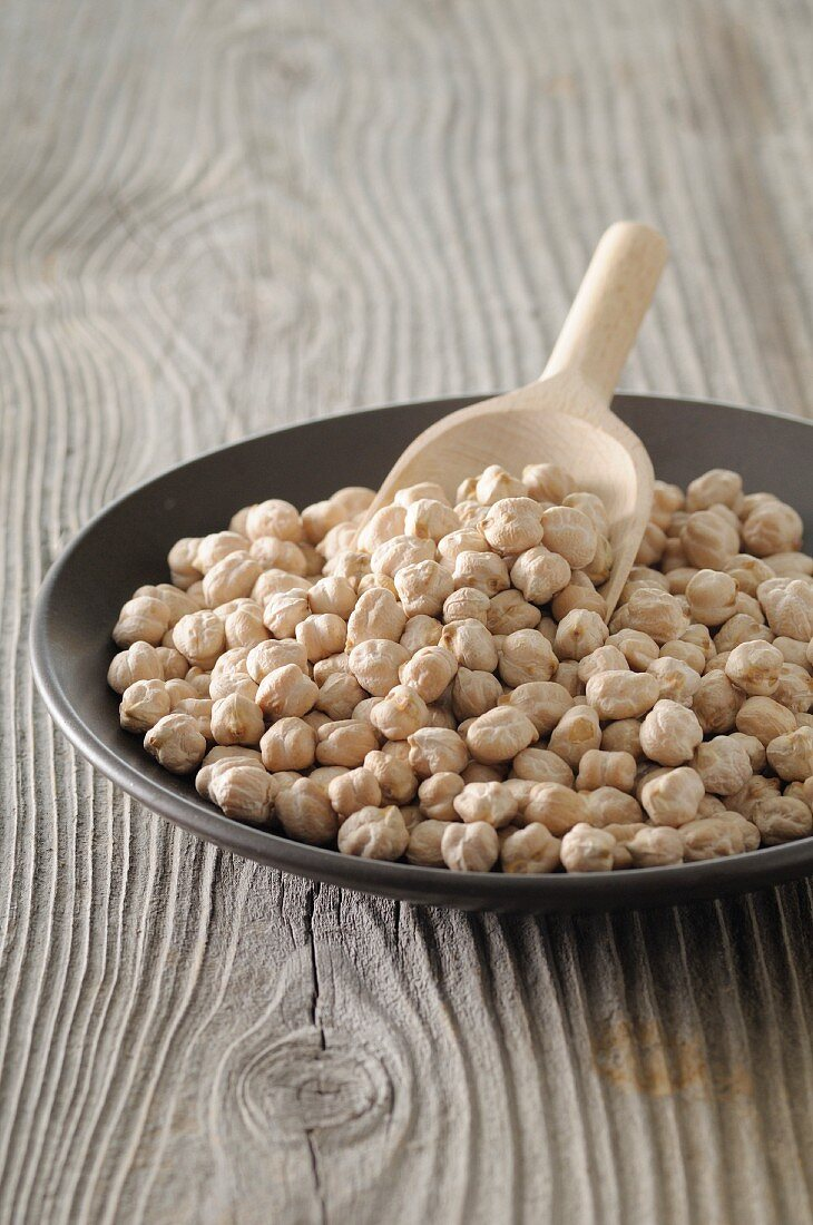 Chickpeas in a bowl with a wooden scoop