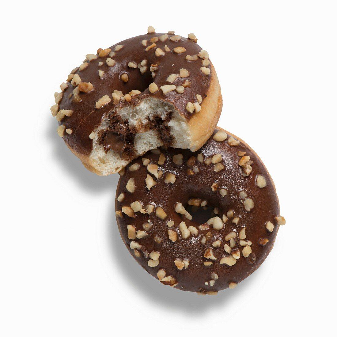 Zwei Nutella-Doughnuts mit Schokoladenglasur und gehackten Haselnüssen, eines angebissen
