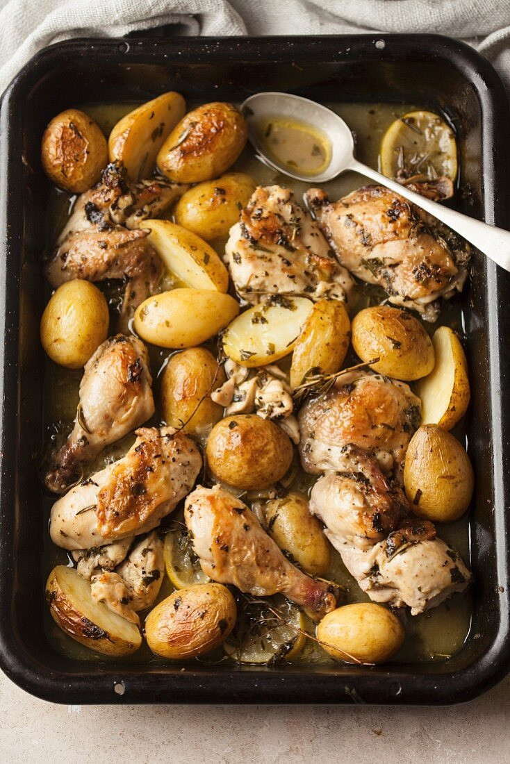 Oven-baked chicken bits with potatoes, lemons and white wine