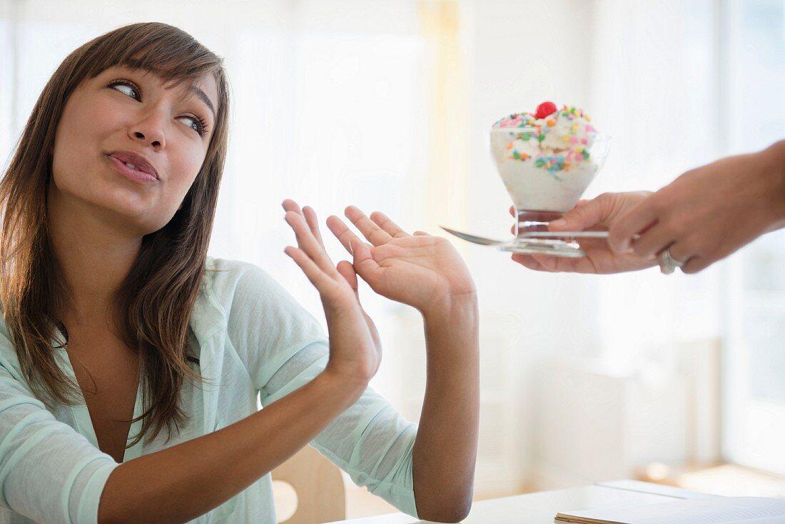 Junge Frau lehnt angebotenen Eisbecher ab