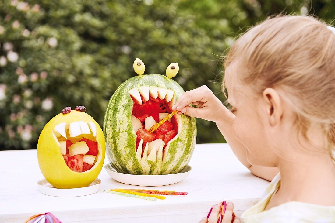 Diced melon served in hollowed out melon shells with a little girl taking a piece with a stick