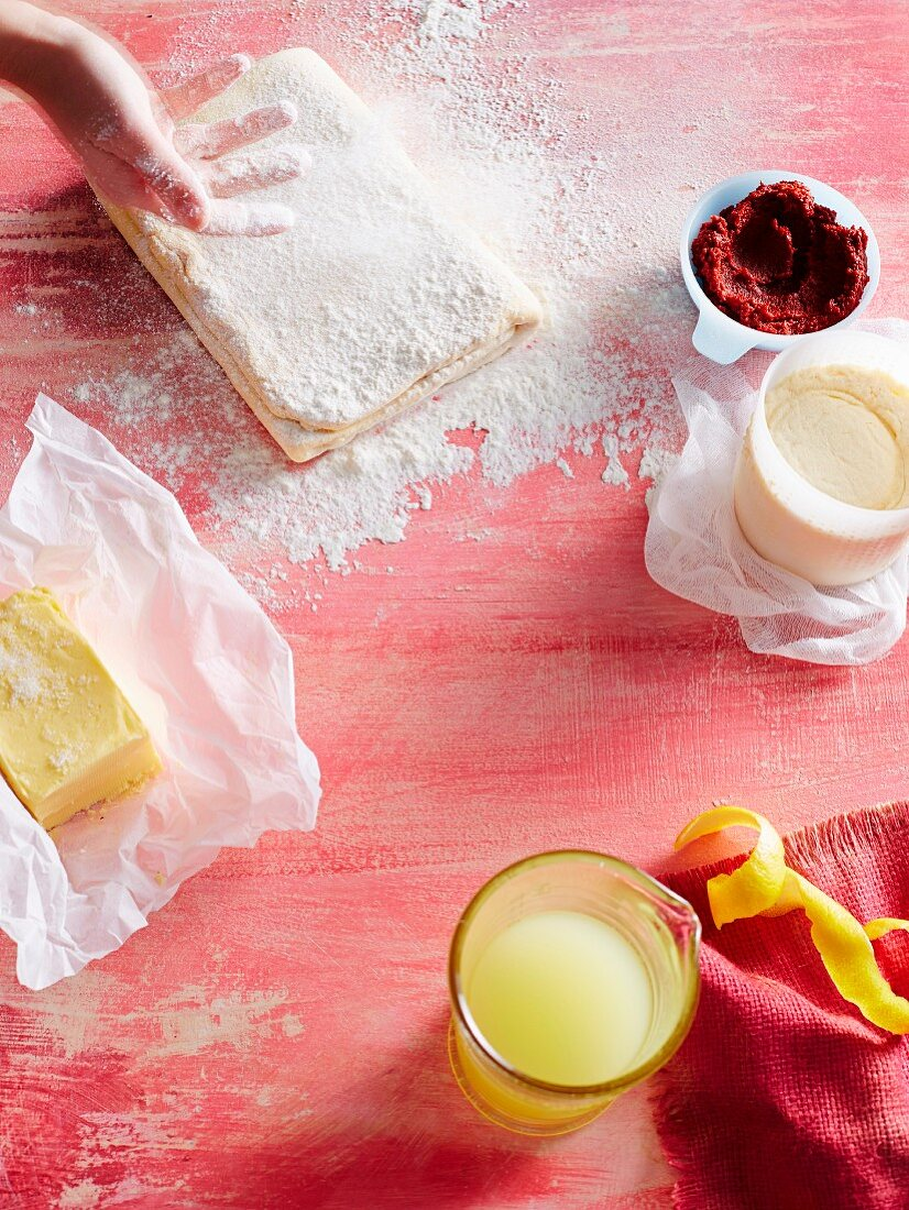 A baking scene with puff pastry, flour, butter and lemon juice