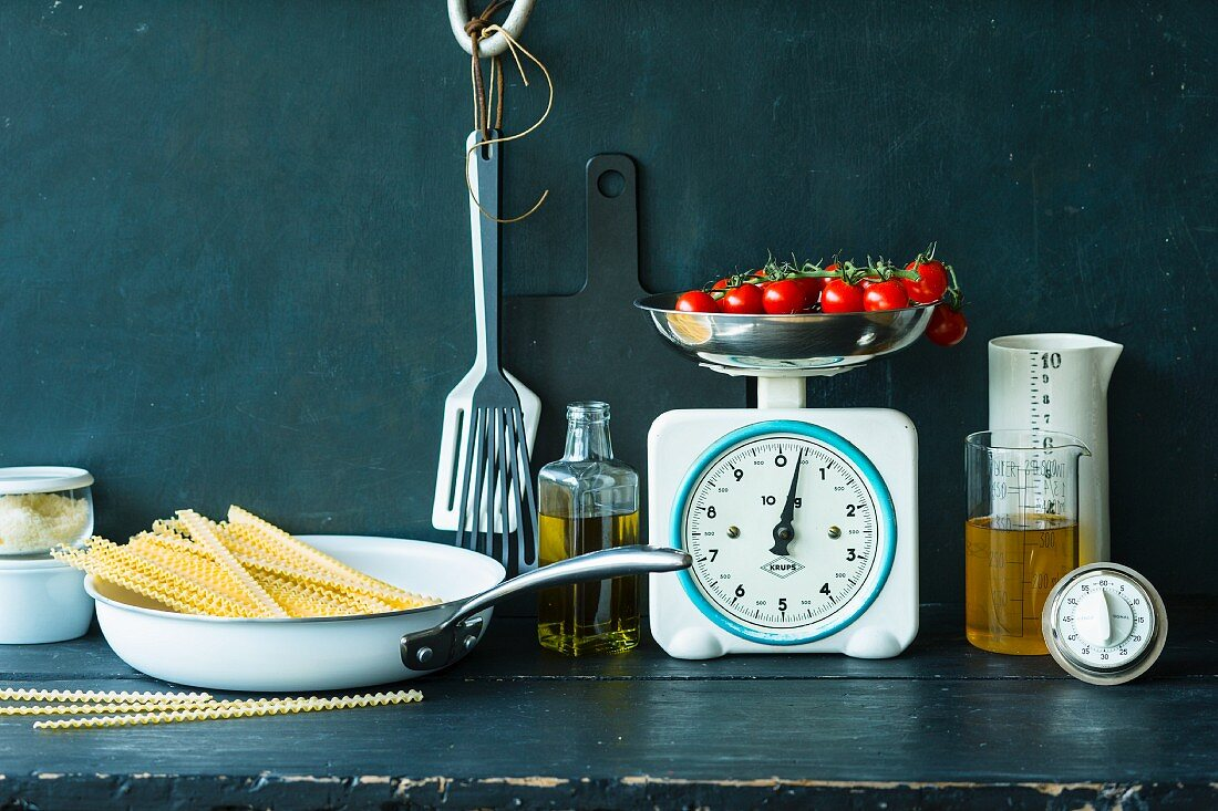 An arrangement of kitchen utensils, pasta, tomatoes and olive oil
