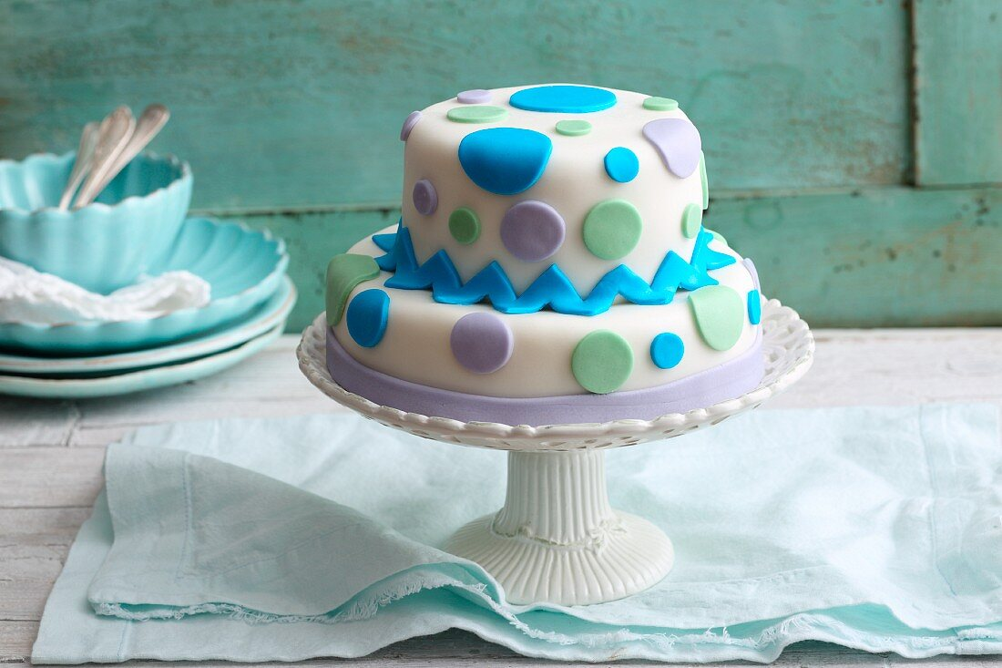 A two-tier chocolate cream cake decorated with fondant icing